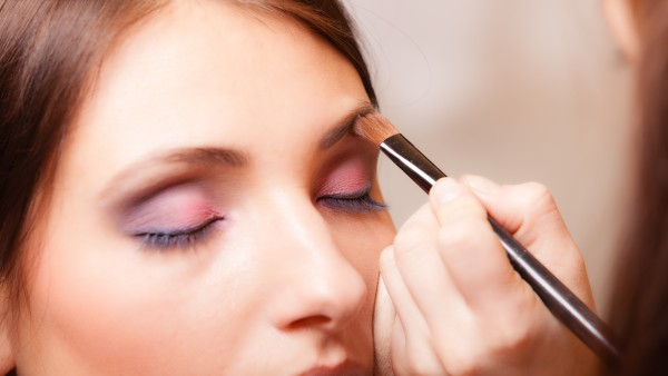 Makeup artist applying with brush cosmetic on eyebrow of woman